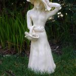 15-inch hand-built, stoneware sculpture of Gaia playing peek-a-boo with a bird, by Peggy Grigor